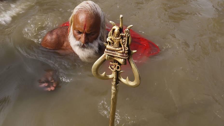 Devoto se banha no Sangam, local de confluência dos rios sagrados Ganges, Yamuna e Saraswatu durante o festival religioso Kumbh Mela na Índia