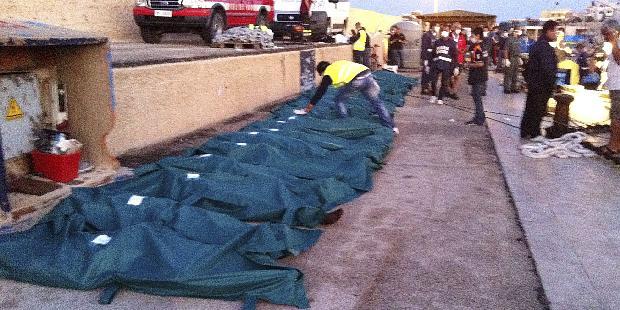Corpos de imigrantes mortos no naufrágio na Ilha de Lampedusa, ao sul da Itália, são enfileirados na costa