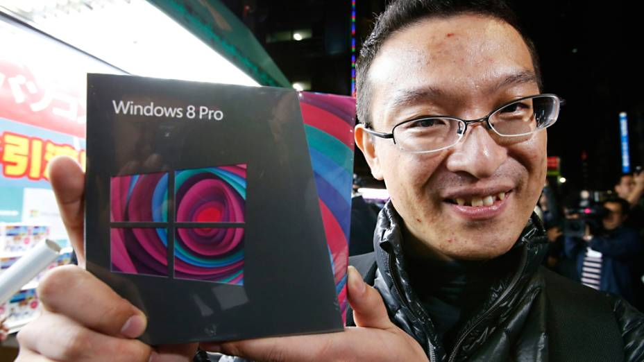 Usuário posa para foto após adquirir o Windows 8 em uma loja de Akihabara, Tóquio