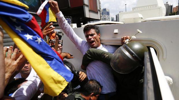 O opositor Leopoldo López é colocado dentro de veículo da Guarda Nacional depois de se entregar à polícia em Caracas, na Venezuela