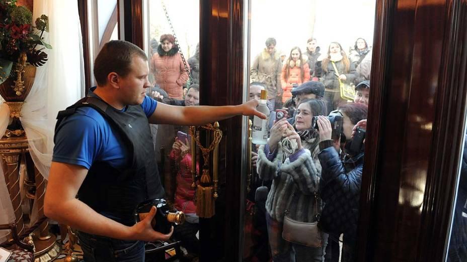 Manifestante que guarda a residência do presidente deposto, mostra uma garrafa de vodca do presidente deposto Viktor Yanukovych foi aberta ao público sábado à noite
