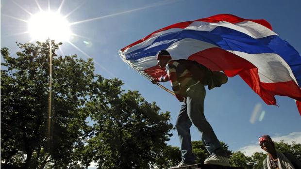 Manifestante segura bandeira da Tailândia em Bangcoc