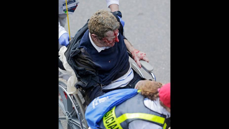 Homem ferido é socorrido por equipes de regaste, após a explosão na maratona de Boston