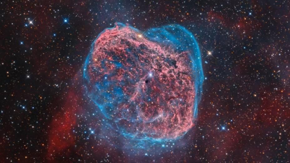 <p>Coração da Nebulosa Crescente brilhando em azul e vermelho. Considerada uma nebulosa de emissão, pois rodeia uma estrela quente, ela é composta pela matéria ejetada de uma estrela poderosa e de vida curta, a Wolf-Rayet, vista no centro da imagem. Radiação ultravioleta e vento estelar aquecem a nuvem, fazendo-a brilhar</p>
