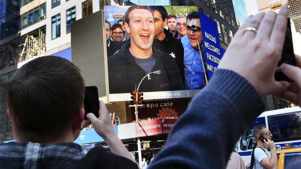 Mark Zuckerberg, fundador do Facebook, aparece em telão em Nova York e pedestres registram momento tirando fotografias na Times Square