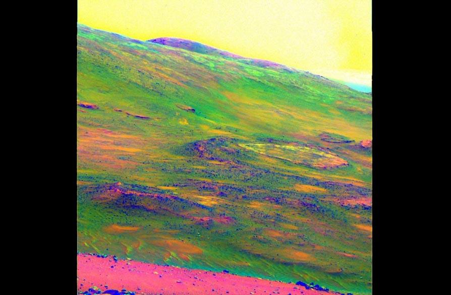 """<p>Imagem do solo marciano com cores trocadas para destacar o desgaste das rochas, em uma região conhecida como """"Home Plate""""</p>"""