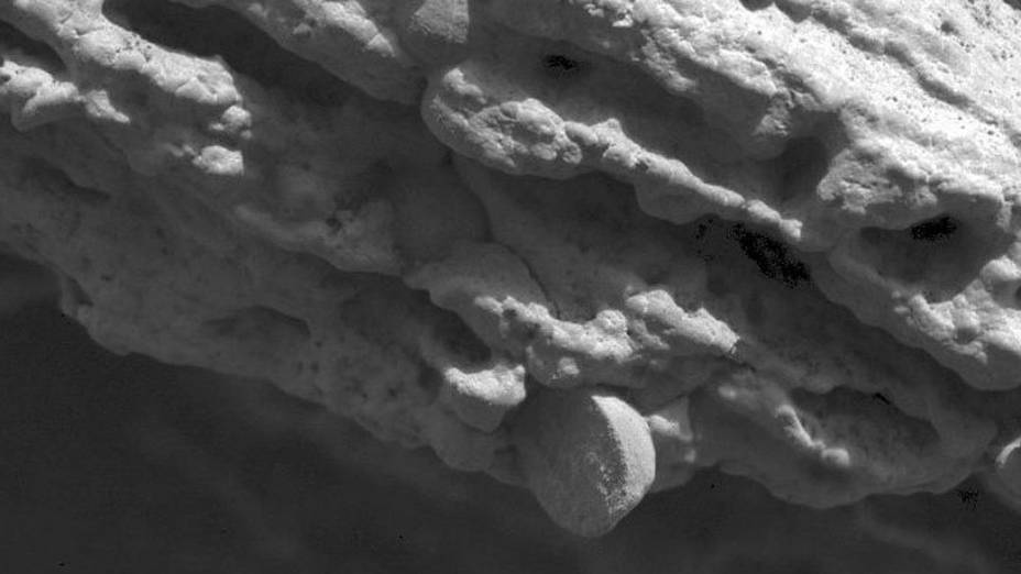 <p>Esferas de hematita presas em camadas de sedimentos finos em uma rocha mostram que as duas estruturas se formaram em momentos diferentes</p>