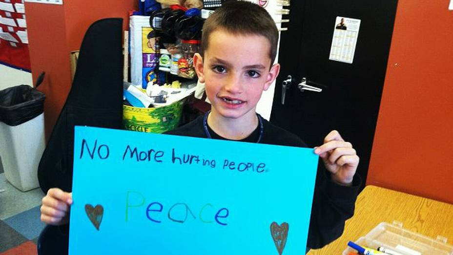 Martin Richard, 8, segura cartaz pedindo paz. O menino é um dos três mortos em atentado, na Maratona de Boston