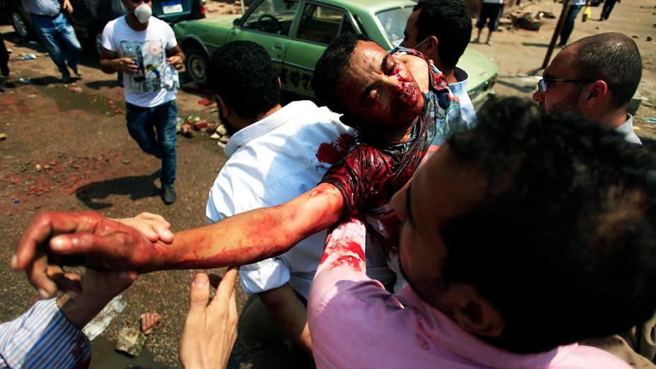 Partidários do presidente deposto do Egito, Mohammed Mursi, carregam um homem ferido pelas forças de segurança egípcias, no Cairo, nesta quarta-feira (14)
