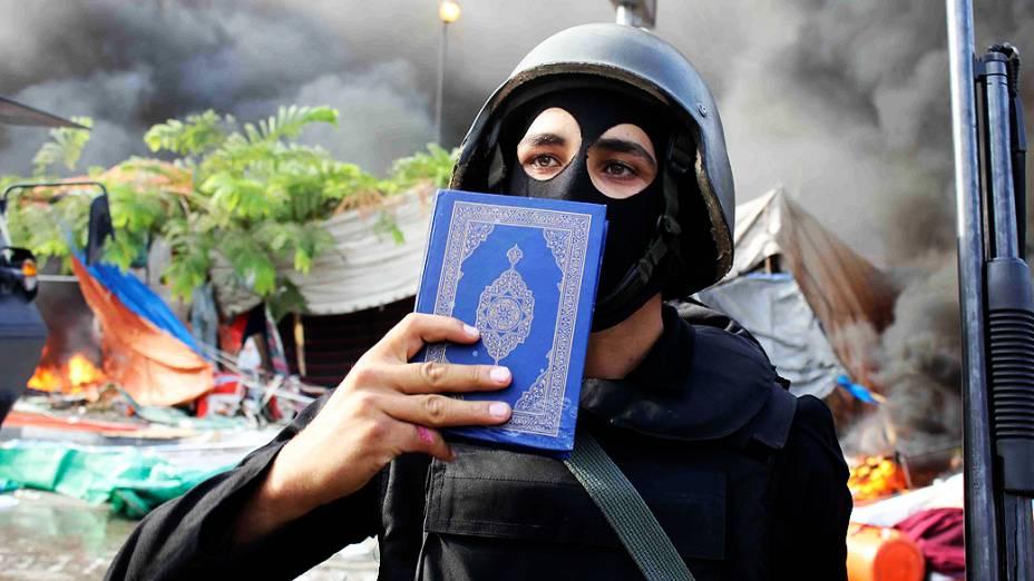 Membro das forças de segurança do Egito segura uma cópia do Alcorão, no Cairo, nesta quarta-feira (14)