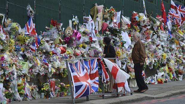 Moradores observam flores colocadas no local onde o soldado britânico Lee Rigby foi destroçado por dois terroristas islâmicos no dia 22 de abril, em Woolwich, sudoeste de Londres