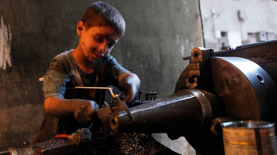 O jovem Issa, 10 anos, ajuda seu pai na fábrica que fornece armamentos para o Exército Livre da Síria, em Alepo