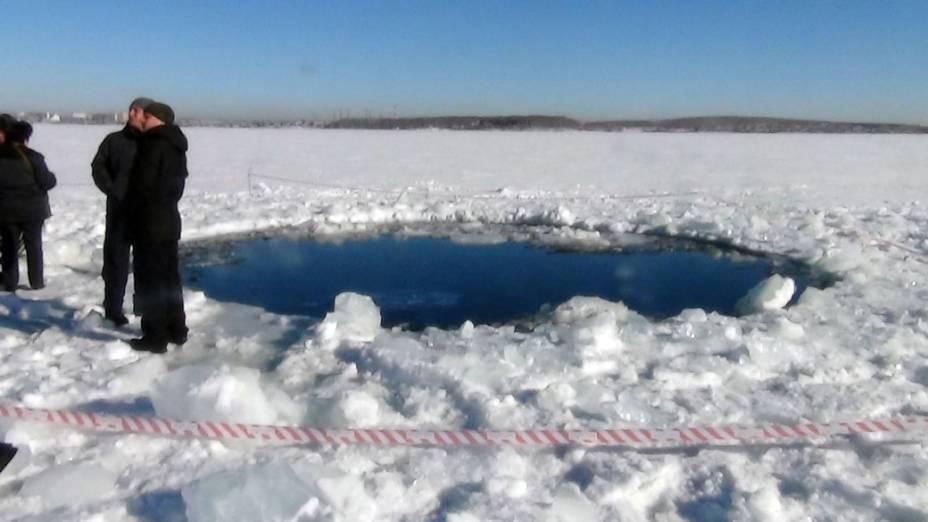 <p>Buraco aberto no gelo pela queda do meteorito na cidade de Tcheliabinsk, na Rússia</p>
