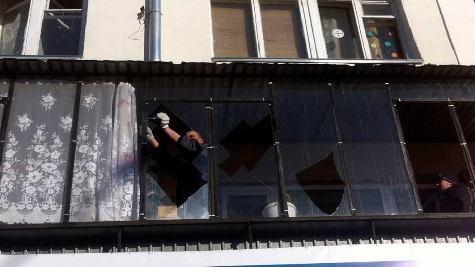 <p>Homem conserta janela danificada pela queda de meteorito na Rússia</p>