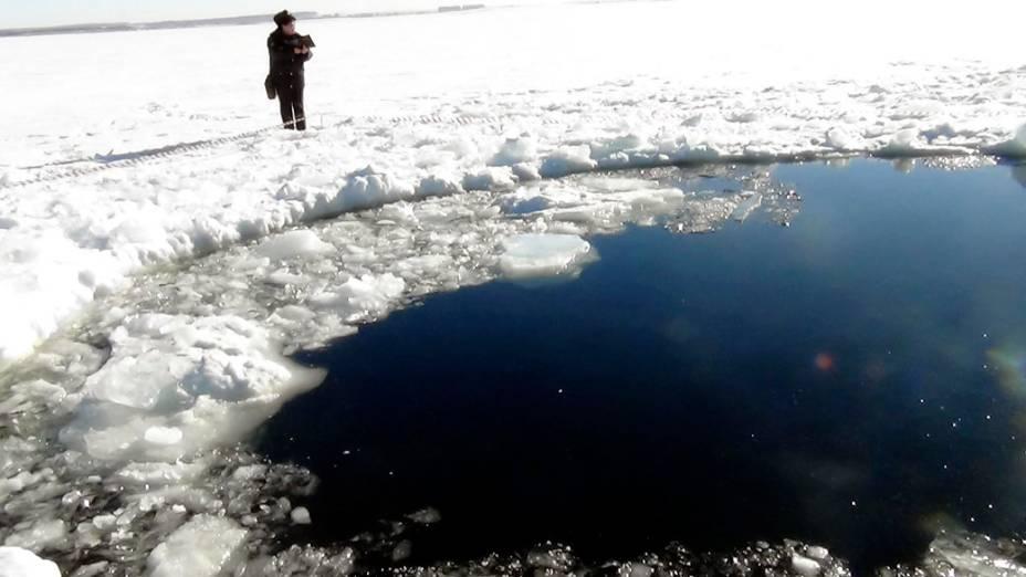 <p>Buraco aberto no gelo pela queda do meteorito na cidade de Chelyabinsk Urais, na Rússia</p>