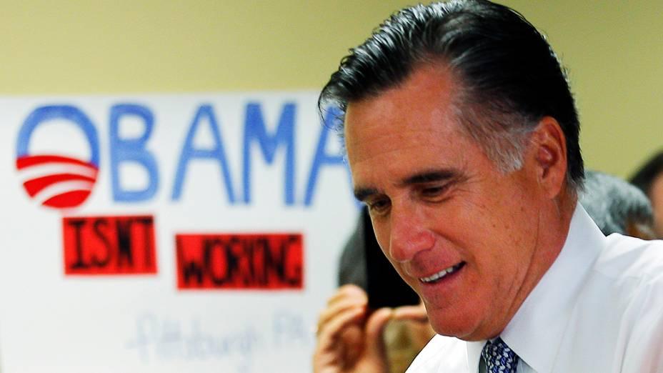 """O candidato republicano, Mitt Romney, passa diante de um cartaz com a frase """"Obama não está trabalhando"""", em Green Tree, Pensilvânia"""