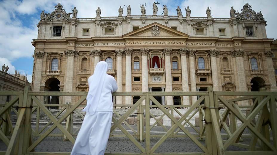 Freira reza na Praça de São Pedro, no Vaticano, durante missa que antecede início do conclave que escolherá novo papa