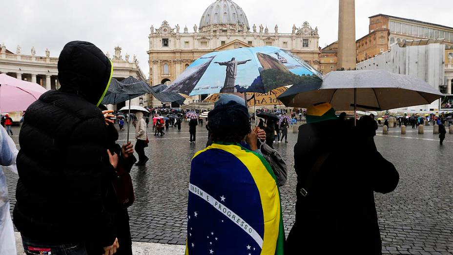 Com a bandeira brasileira e um guarda-chuva com a imagem do Rio de Janeiro, pessoas acompanham a chegada dos 115 cardeais eleitores à Capela Sistina, no Vaticano