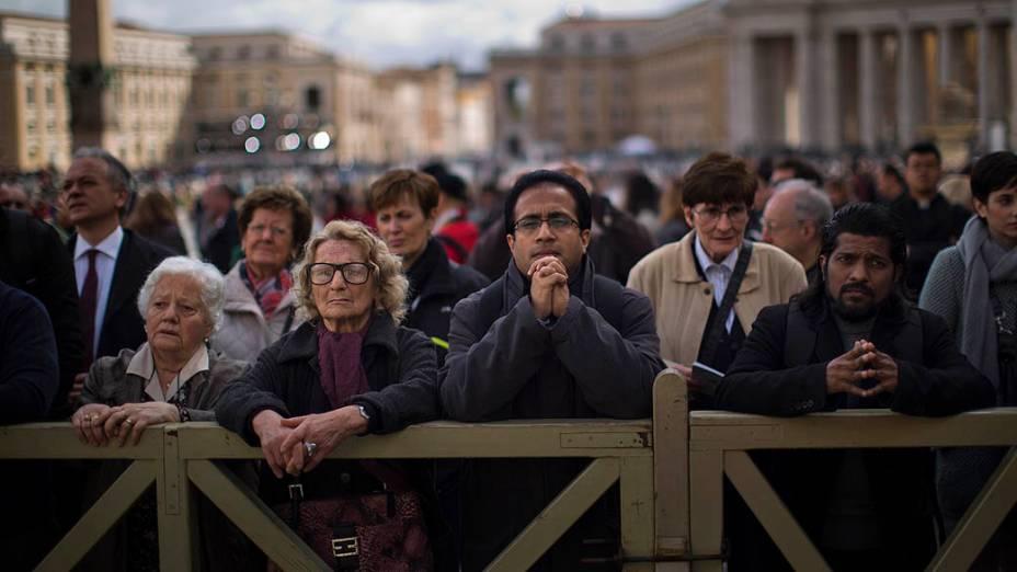 Fiéis fazem orações na Praça de São Pedro, no Vaticano, durante a missa que abre o conclave