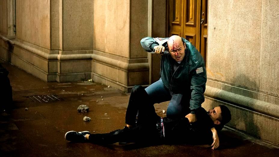 O PM Wanderlei Vignoli aponta uma arma para os manifestantes que o agrediram, após ele deter um homem que pichava o prédio do Tribunal de Justiça