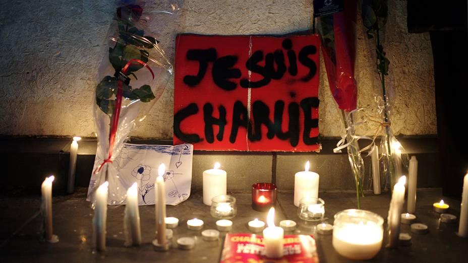 """Velas são colocadas diante de um cartaz com a mensagem """"eu sou Charlie"""", em homenagem às vítimas do ataque feito por homens armados e encapuzados que abriram fogo e mataram ao menos 12 pessoas na sede da revista Charlie Hebdo, em Paris"""