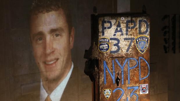 Imagem de uma das vítimas dos ataques de 11 de setembro de 2001 é projetada ao lado de coluna retirada das torres do WTC