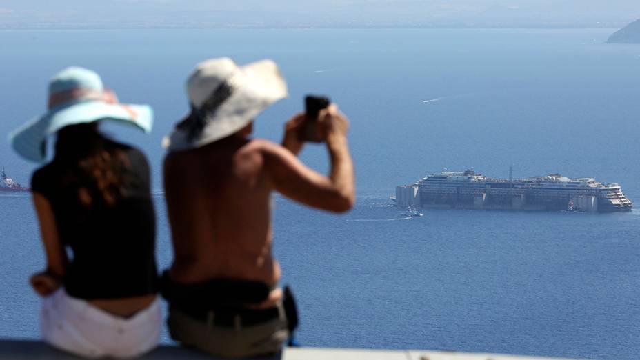 Turistas fotografam os restos do navio naufragado Costa Concordia, próximo a Ilha de Giglio, região central da Itália