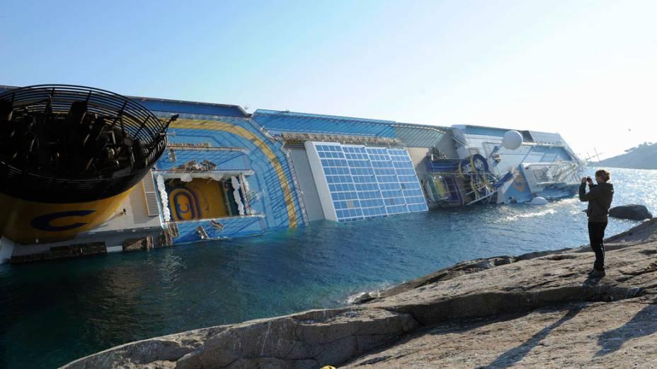 Homem fotografa o transatlântico Costa Concordia, durante o naufrágio na ilha de Giglio, na Itália - 14/01/2012