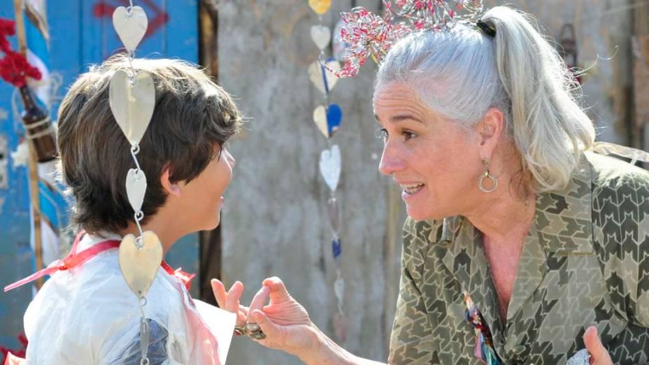 Batata (Bernardo Simões) pergunta por Rita (Mel Maia) enquanto Lucinda (Vera Holtz) termina de arrumá-lo