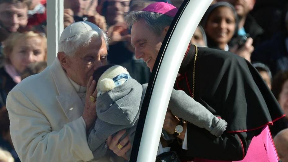 O papa Bento XVI beija uma criança observado por seu secretário, Georg Gaenswein, na Praça de São Pedro, no dia de sua última audiência pública