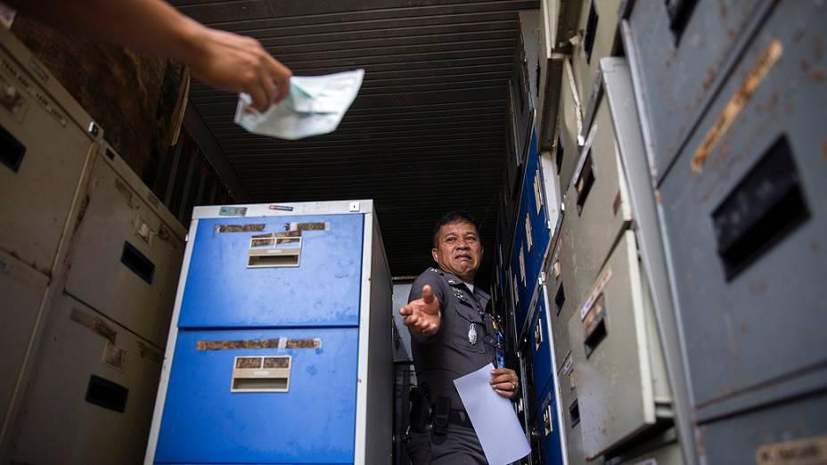 Bens pessoais de vítimas do tsunami de 2004 são retirados de um contêiner de três metros de altura e 12 de comprimento em uma delegacia de polícia em Takua Pa, na província de Phang Nga, na Tailândia