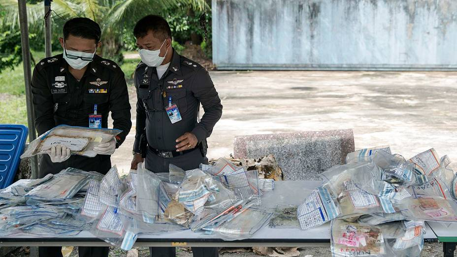 Policiais separam malas cheias de objetos de vítimas do tsunami de 2004 em uma delegacia em Takua Pa, na província de Phang Nga, na Tailândia