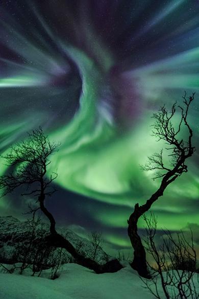 <p>Aurora boreal. A foto foi tirada no dia em que uma ejeção de massa coronal (grande quantidade de gás ionizado a altas temperaturas) atingiu a Terra, propiciando o aparecimento das cores no céu</p>