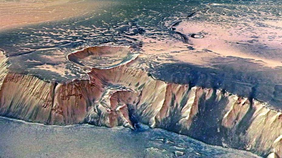 <p>Outro ângulo do gigantesco Echus Chasma, uma das maiores regiões de fonte de água em Marte. Mostra um penhasco impressionante, com 4.000 metros de altura. Cientistas acreditam que cachoeiras colossais já derramaram suas águas através do penhasco há centenas de milhões de anos. O solo, incrivelmente plano, foi inundado por lava basaltica.</p>