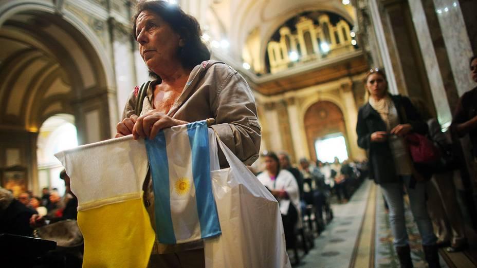 Fiel assiste à missa segurando a bandeira da Argentina na Catedral Metropolitana, em Buenos Aires