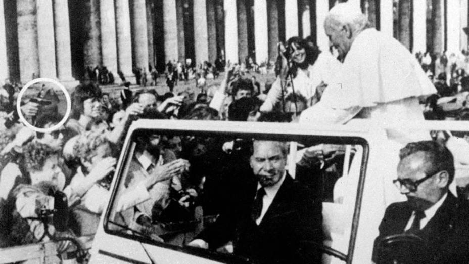 1981 – O Papa João Paulo II momentos antes de ser baleado na praça São Pedro, no Vaticano. No detalhe, a arma de Ali Agca