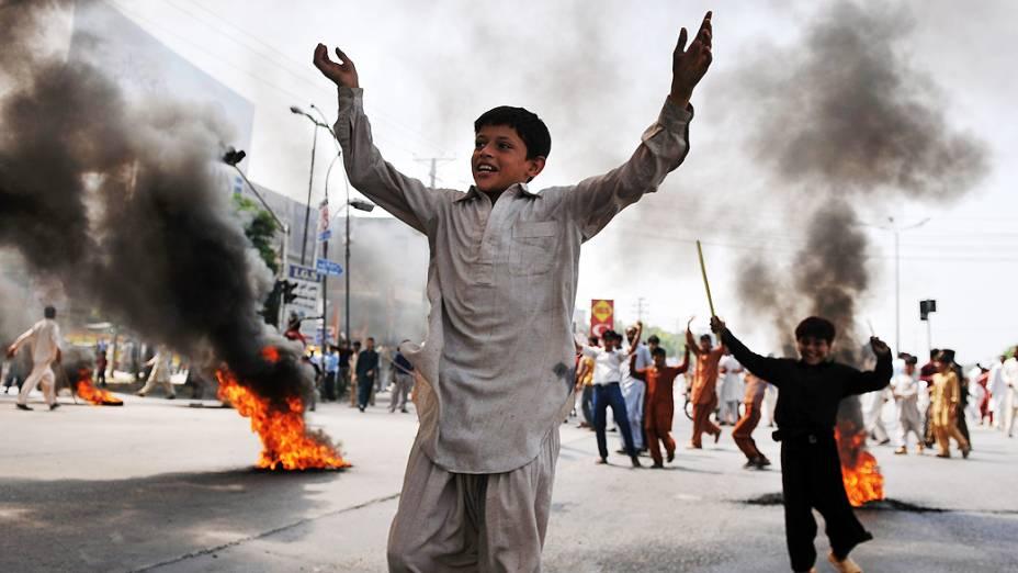Crianças brincam em meio às barricadas de fogo durante protesto de muçulmanos em Rawalpindi, no Paquistão, em protesto contra o filme anti-islâmico