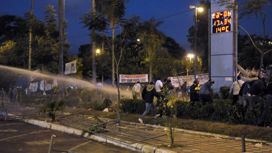 Policiais dispersam com jato dàgua partidários do presidente deposto Fernando Lugo, no Paraguai
