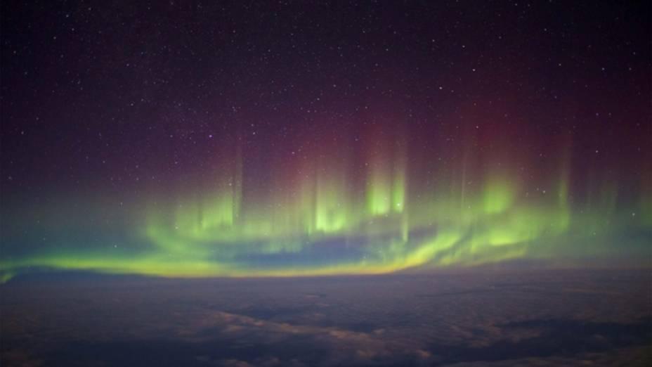 <p>Aurora vista da janela de um voo transatlântico entre Londres e Nova York, em fevereiro de 2014. O fotógrafo equilibrou a câmera sobre sua mochila para conseguir fazer a foto</p>