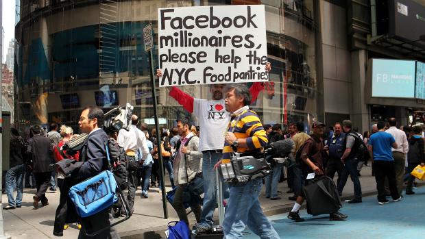 Pedestre segura cartaz em frente à Nasdaq pedindo para que novos milionários do Facebook contribuam na distribuição de alimentos em Nova York