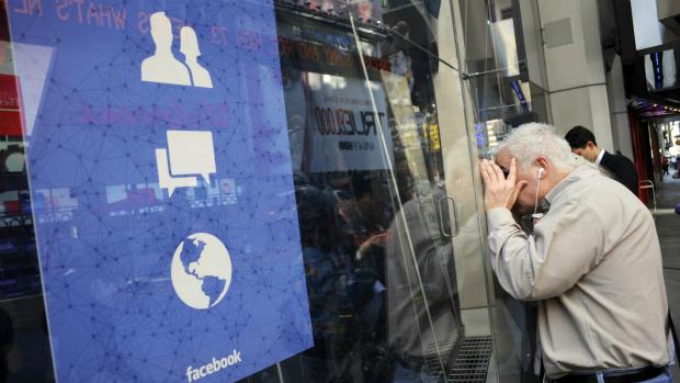 Pedrestre observa janela do prédio da Nasdaq, em Nova York, onde acontece a estreia do Facebook no mercado financeiro