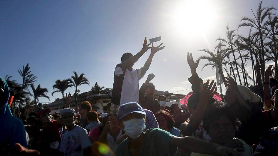 Sobreviventes tentam pegar comida distribuída pelos soldados filipinos no aeroporto de Tacloban