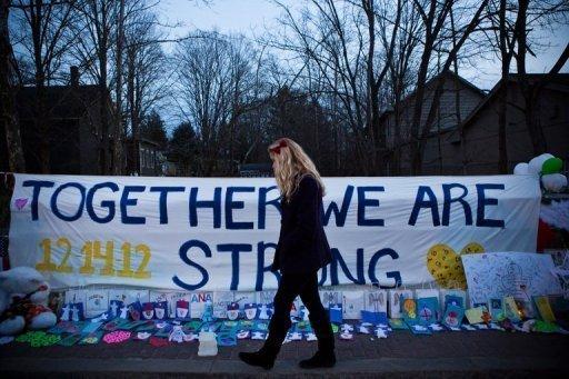 Mulher passa em frente a memorial criado em homenagem às vítimas da escola Sandy Hook