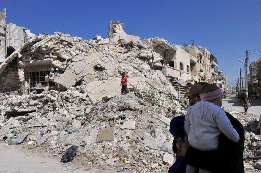 Família síria examina destroços em Maarat al-Numan, Síria, em 20 de março de 2013
