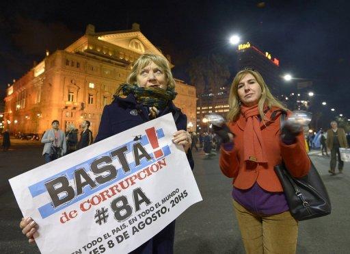 Mulher segura cartaz contra a corrupção durante protestos em Buenos Aires
