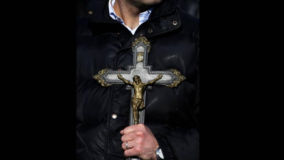 Fiel Segura crucifixo enquanto aguarda última audiência geral do Papa Bento XVI, no Vaticano