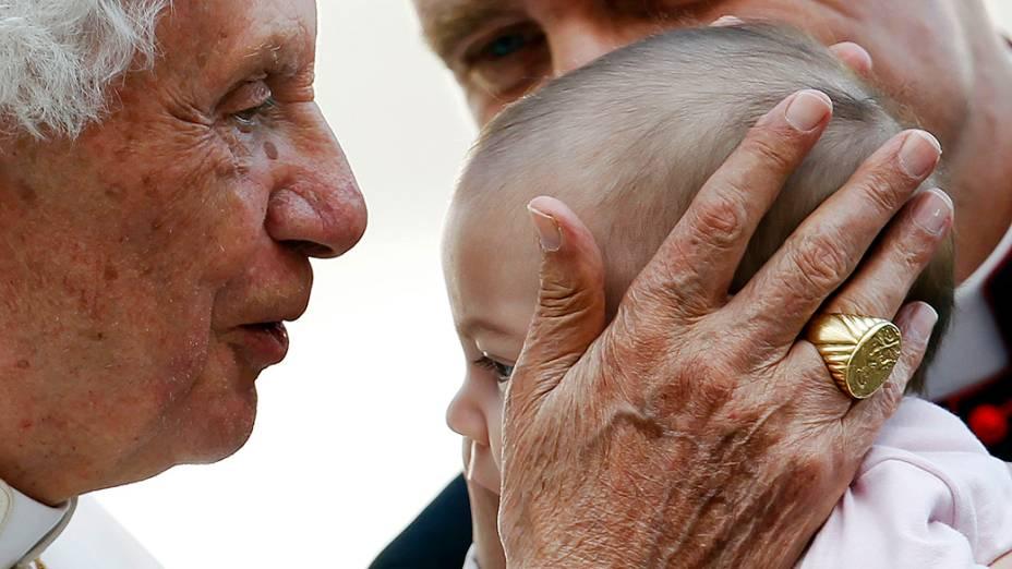 O Papa Bento XVI beija criança durante audiência no Vaticano