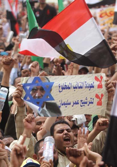 Manifestante segura cartaz com foto de Omar Suleiman, ex-vice-presidente e chefe da inteligência no mandato de Mubarak, durante protesto na praça Tahir no Cairo, Egito