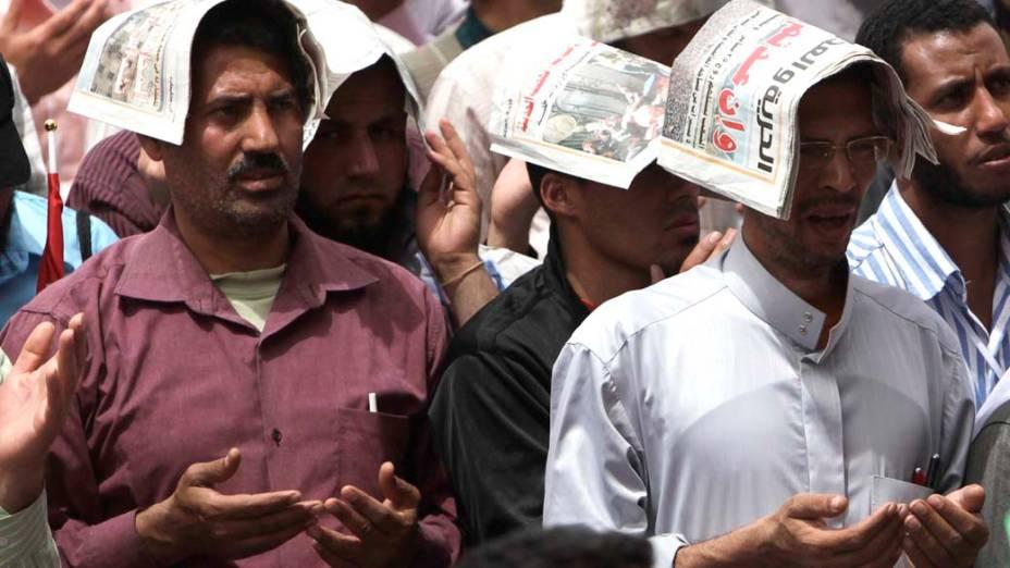 Manifestantes se protegem do sol durante a reza de sexta-feira na praça Tahrir
