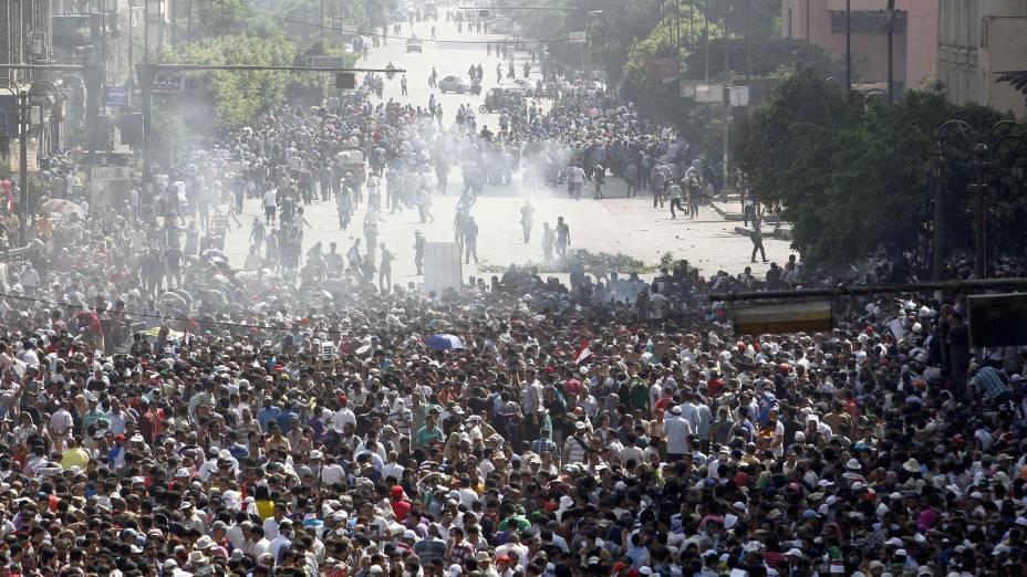 Manifestantes correm após bomba de gás lacrimogêneo ser disparada contra protesto no Cairo
